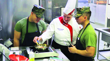 A chef teaching two soldiers how to cook