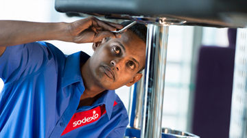 A Sodexo employee repairing kitchen equipment