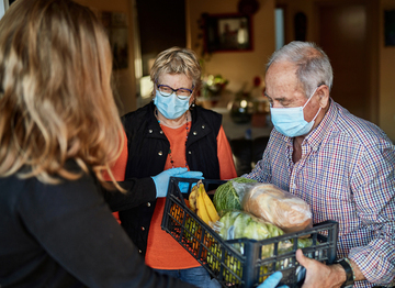 home delivery of groceries to elderly couple wearing masks
