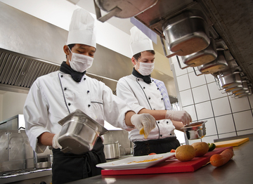Chefs wearing masks whilst preparing food in the kitchen