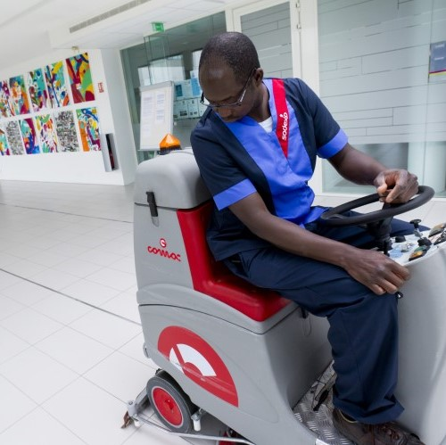 Sodexo facilities employee on ride-on floor cleaning machine